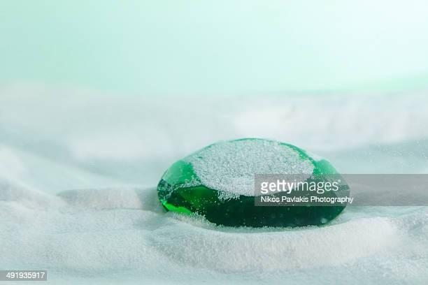 Green emerald sunk through the sand.