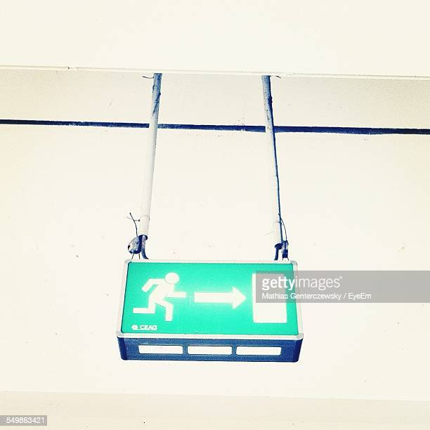 Green Exit Sign Hanging On Wall
