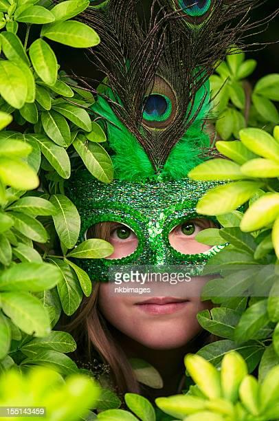 Fille aux yeux verts dans le masque de paon stares à feuilles