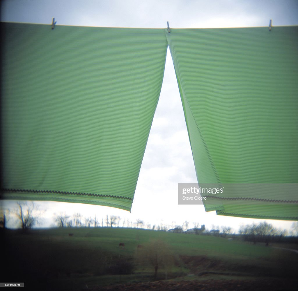 Green fabric hanging on clothesline to dry : Stock Photo