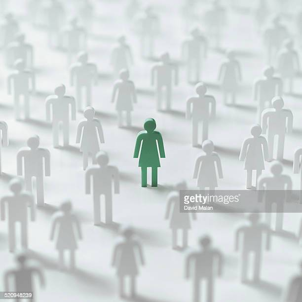 Green female figure in a crowd of white figures