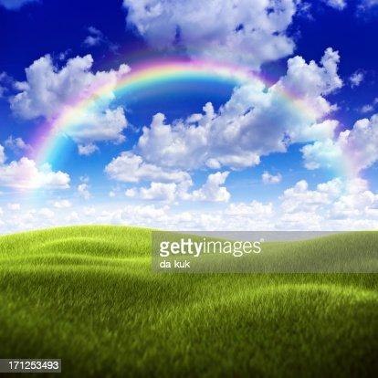 Green field over moody sky and rainbow