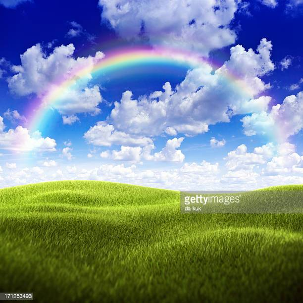 Green field over moody sky and rainbow