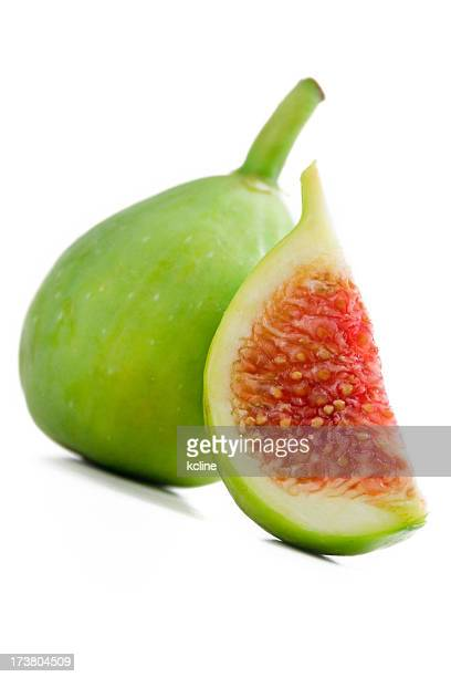 Green fig and a slice with red fruit over white background