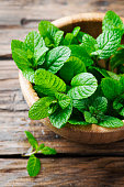Green fresh mint om the wooden table, selective focus