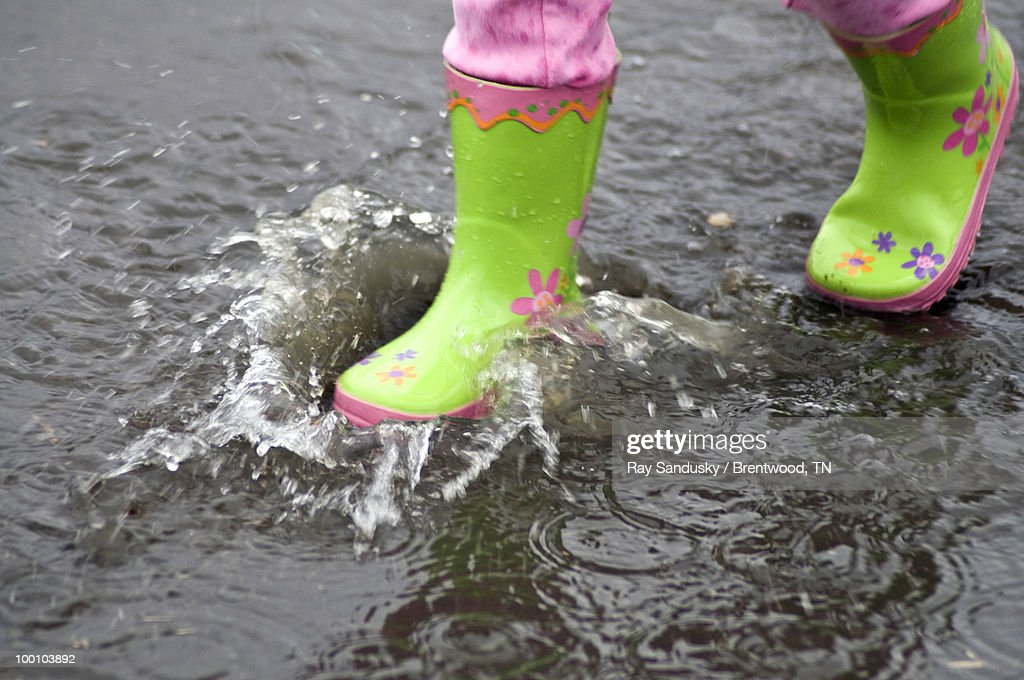 Green Galoshes Splashing In A Puddle : Stock Photo