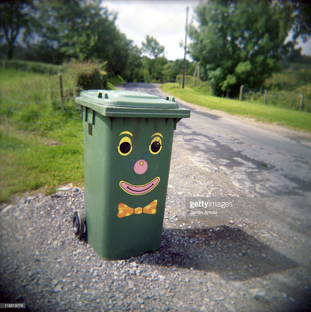 green garbage bin with smiley face stock photo