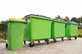 Four green garbage containers standing diagonally in a row