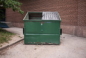 Damaged dark green dumpster near a brick building.