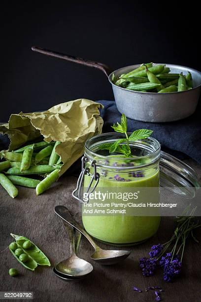 Green gazpacho in jar with peas and lavender on wooden table with vintage colander and spoons