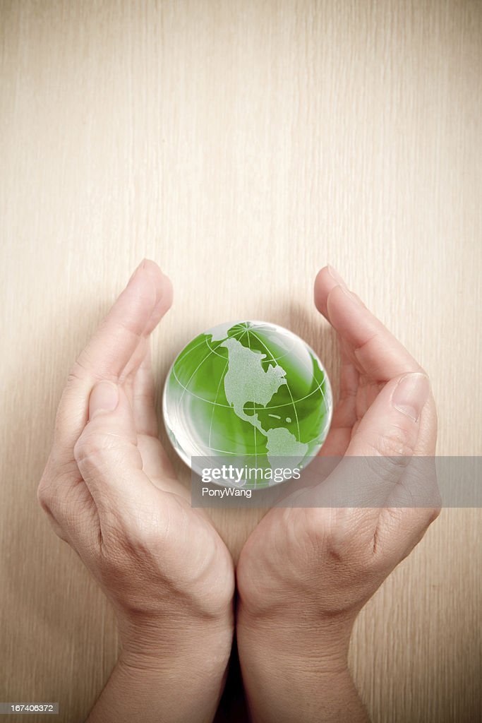 Green glass globe in hand : Stock Photo