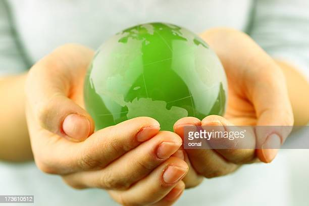 Green globe being held by a person's hands