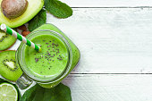 green healthy smoothie with avocado, spinach, kiwi, lime and chia seeds in a glass jar with a straw over white wooden background. top view with copy space. shallow depth of field