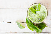 Filtered photo of green herbal detox drink made of spinach on white wood. Healthy lifestyle, diet background. Text space