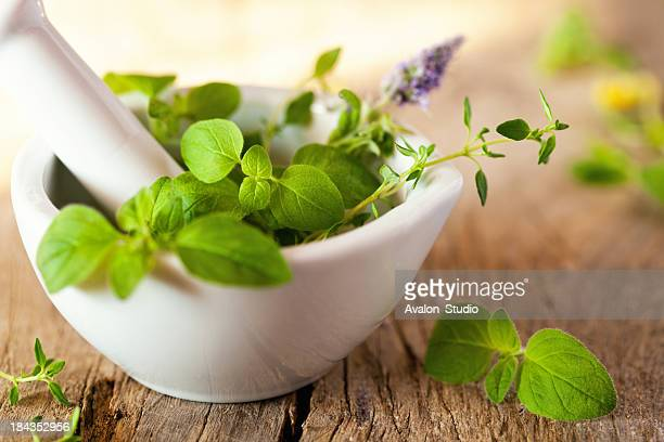 Green herbs in a white mortar. On a wooden plank.