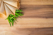 Green hot chili peppers in wafer cones on wooden background