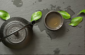 Green japanese tea on black slate background. Black teapot and bowl with green tea. Top view with copy space.