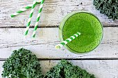 Green kale smoothie overhead view, in a glass with straw on an aged wood background