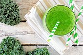 Green kale smoothie overhead view, in a glass with straw on a striped cloth against aged wood