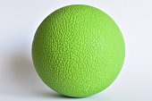 Green lacrosse ball closeup with rough surface pattern, isolated photo with white background, used for massage and muscle pain relief