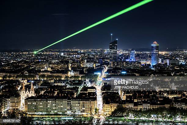A green laser ray is emitted above Lyon to calculate the variations of light speed in the atmosphere on September 24 2015 AFP PHOTO / JEFF PACHOUD