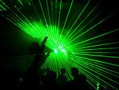 Green lasers in a club with the shadow of some clubbers