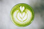 Trendy green latte, macro. Avocado or matcha foam with latte art.