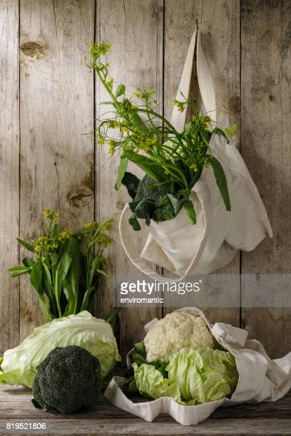 Green leafy vegetables in a natural cotton reusable bag hanging from a hook on an old weathered wooden plank wall.