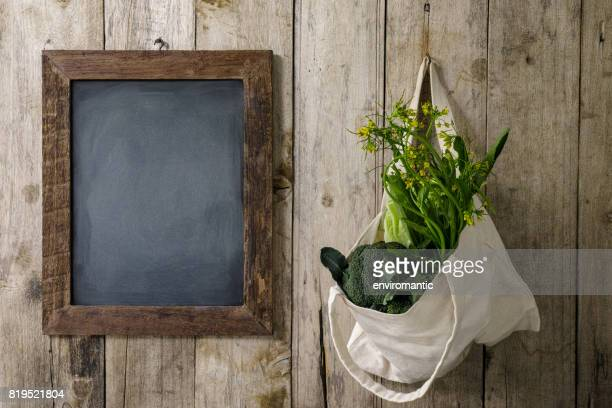 Green leafy vegetables in a natural cotton reusable bag next to a wooden framed blank blackboard.