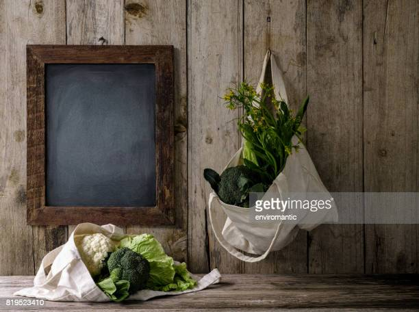 Green leafy vegetables in a natural cotton reusable shopping bags next to and below a wooden framed blank blackboard.