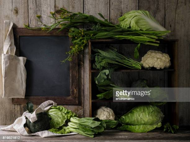 Green leafy vegetables on old rustic wooden shelves and an old weathered table next to a wooden framed blank blackboard with a resusable cotton shopping bag hanging from a corner of the frame.