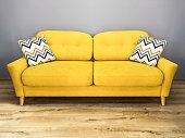 Green lemon yellow sofa with pillow. Soft lemon couch. Modern divan in interior gray wall wooden floor.