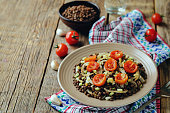 Green Lentil roasted onion and tomato salad on a wood background. toning. selective focus