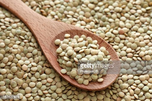Green lentils in a wooden spoon