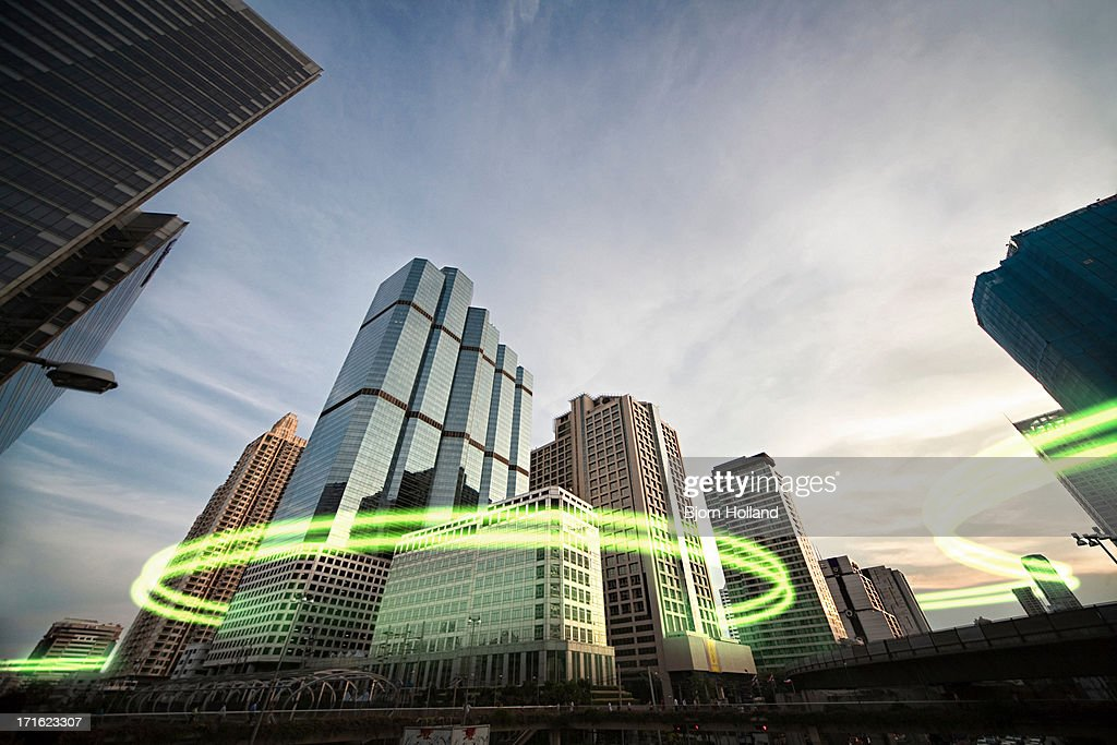 Green light trails surrounding skyscrapers : Stock Photo