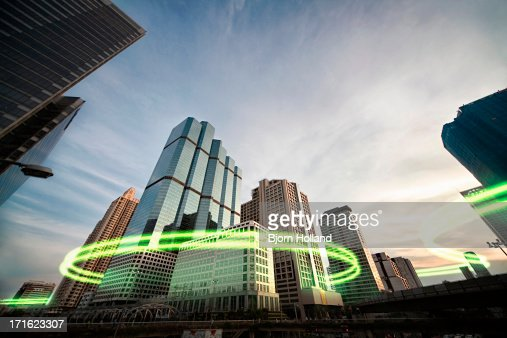 Green light trails surrounding skyscrapers