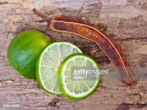 Green limes and tamarind on wooden background. : Bildbanksbilder