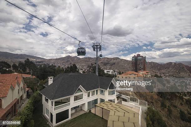 A green line Mi Teleferico cable car travels above the San Alberto neighborhood of La Paz Bolivia on Sunday Sept 4 2016 Boliva's Mi Teleferico cable...