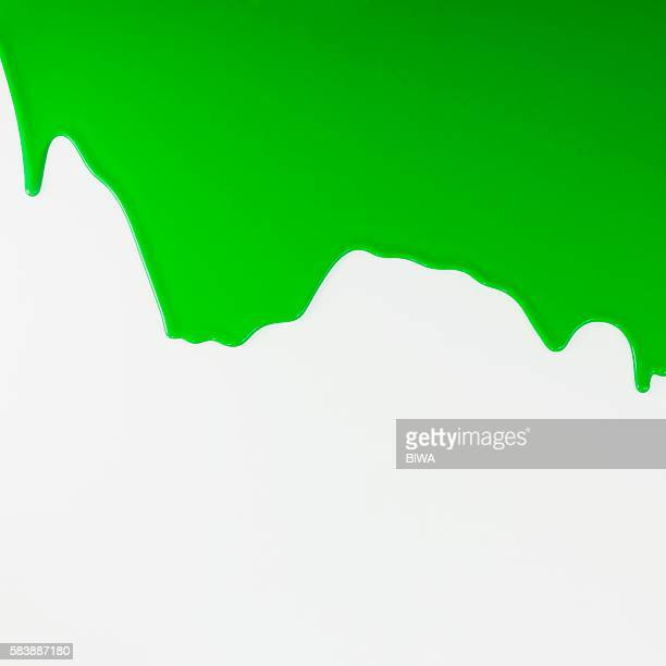 Green liquid dripping on white surface
