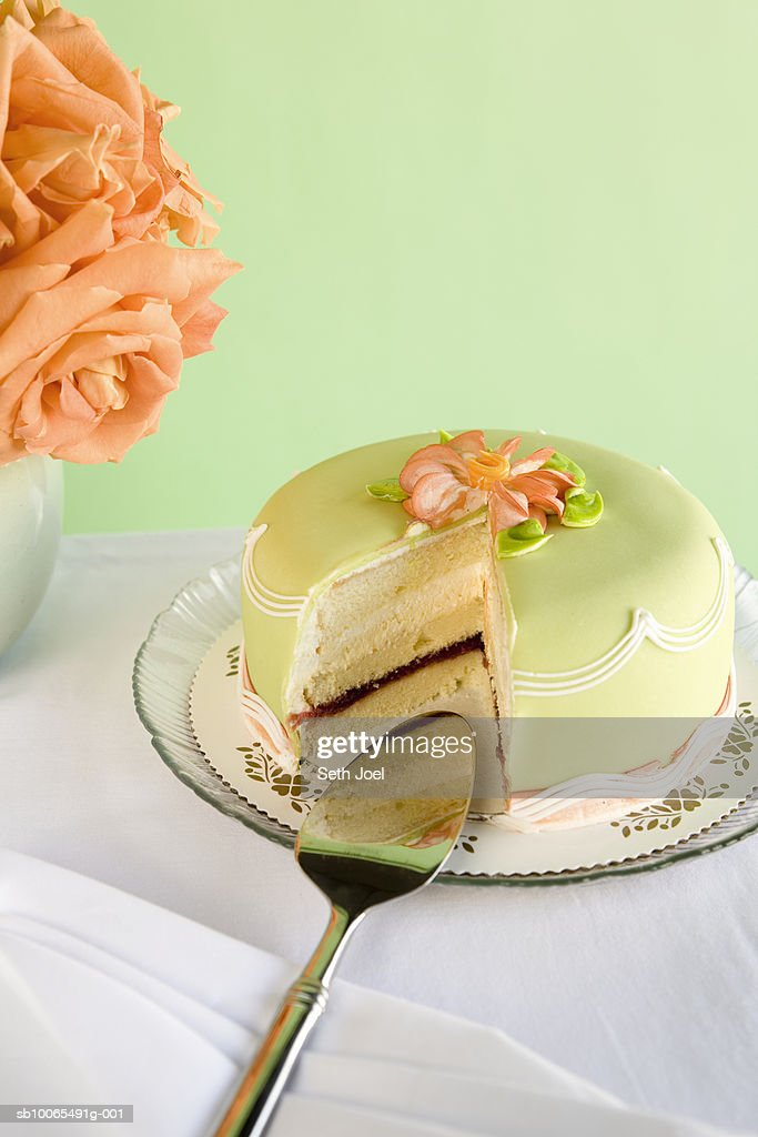 Green marzipan cake with missing slice on table with roses : Stock Photo