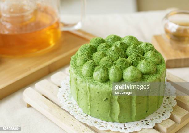 A green matcha cake and a pot of tea on the table
