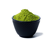 green matcha tea powder in black bowl isolated on white background