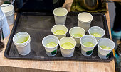 Green milk tea sample in mini white plastic tasting cup on black tray. Marketing promotion for new launched flavor of healthy product.
