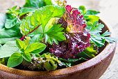 Fresh organic green mixed salad leaves over rustic wooden background close up