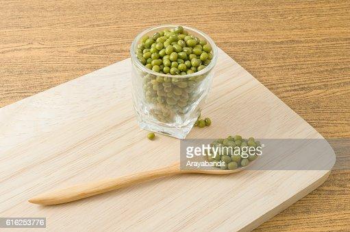 Feijão Mung Verde em colher e copo de vidro : Foto de stock