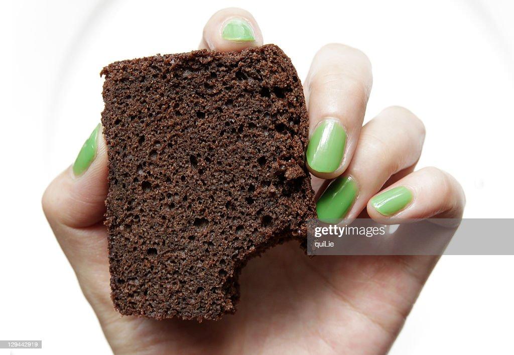 Green nail hand holding chocolate cake : Stock Photo