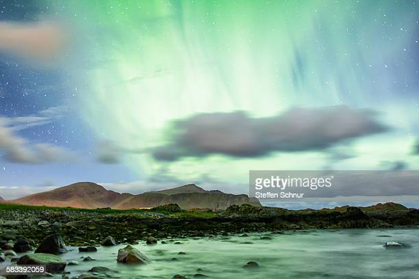 Green northern lights over the rocky coast Norway