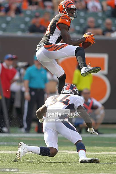 J Green of the Cincinnati Bengals jumps over the attempted tackle by Will Parks of the Denver Broncos during the fourth quarter at Paul Brown Stadium...