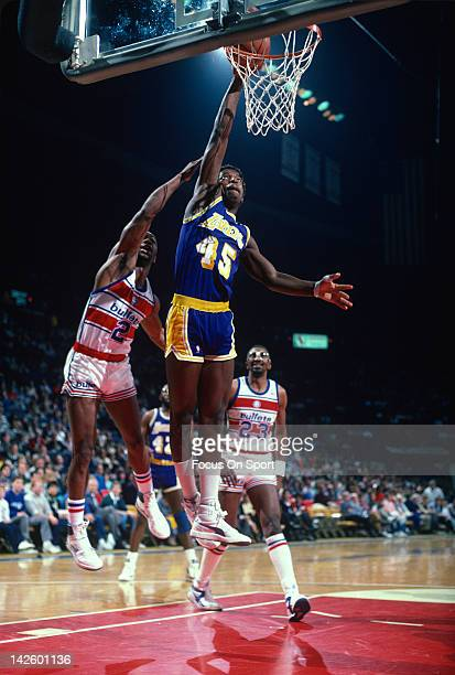 C Green of the Los Angeles Lakers jams the ball over Ennis Whatley of the Washington Bullets during an NBA basketball game circa 1986 at the Capital...