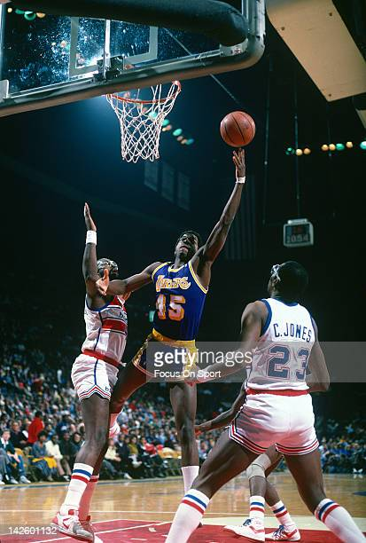 C Green of the Los Angeles Lakers shoots over Moses Malone and Charles Jones of the Washington Bullets during an NBA basketball game circa 1986 at...